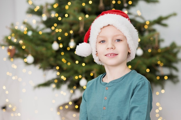 Retrato de uma linda criança com roupas de natal em frente a uma árvore de natal decorada