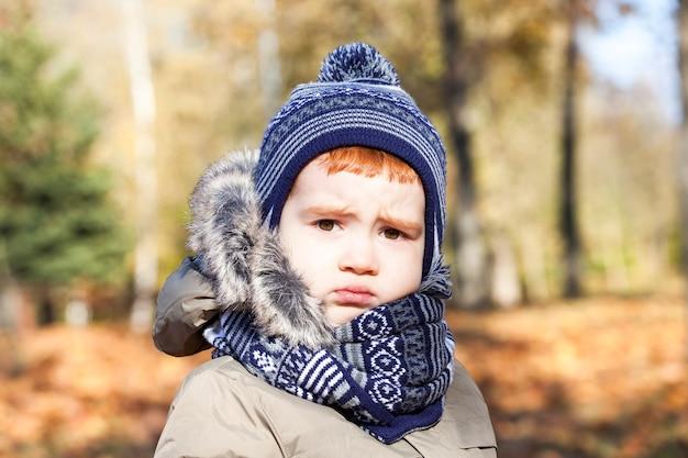 Retrato de uma linda criança com uma expressão chateada no rosto. o menino está vestido com roupas quentes, temporada de outono. close da foto.