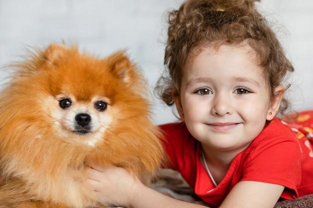 Retrato de uma linda criança posando com seu cachorro