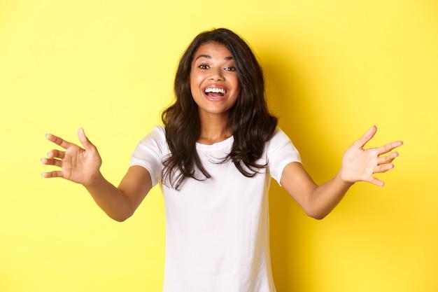 Retrato de uma linda e simpática garota afro-americana estendendo as mãos para você e querendo segurar