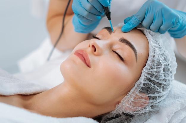 Retrato de uma linda e simpática mulher deitada de olhos fechados durante um procedimento dermatológico