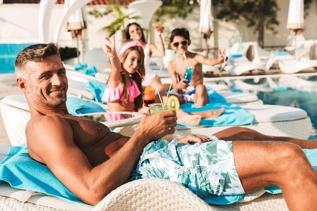 Retrato de uma linda família alegre com crianças, deitadas em espreguiçadeiras perto da piscina em frente ao hotel, bebendo coquetéis