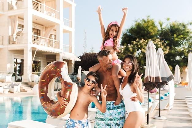 Retrato de uma linda família alegre com crianças, descansando perto de uma piscina luxuosa e se divertindo com um anel de borracha fora do hotel