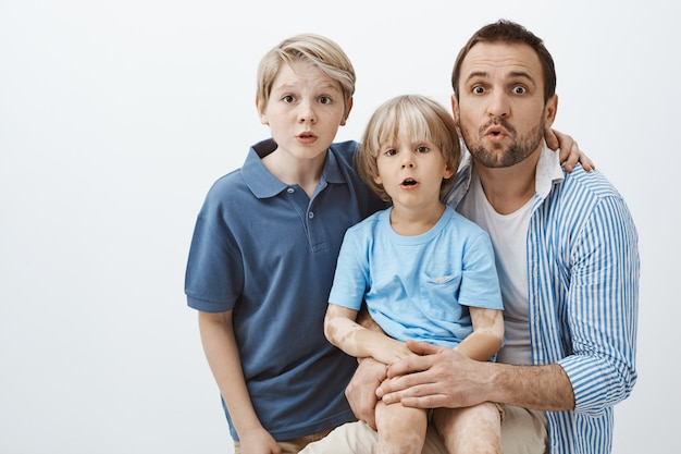 Retrato de uma linda família de filhos e pai, abraçando e surpreso de pé