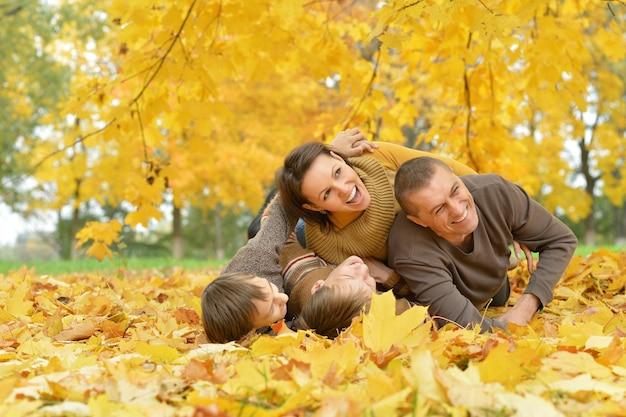Retrato de uma linda família feliz deitada no parque outono