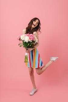 Retrato de uma linda feliz alegre sorridente jovem mulher bonita posando isolada sobre uma parede rosa segurando flores