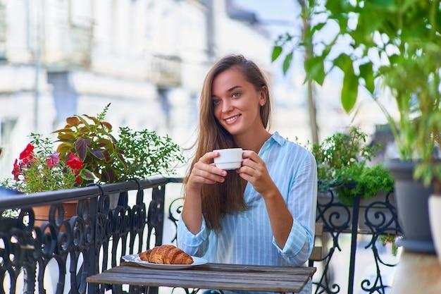 Retrato de uma linda feliz fofa alegre sorridente mulher romântica com uma xícara de café aromático nas mãos e um prato de croissant fresquinho na mesa pela manhã em uma varanda