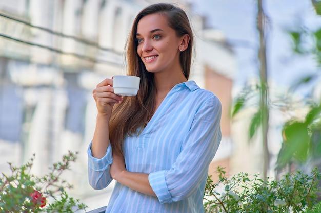 Retrato de uma linda feliz fofa alegre sorridente mulher romântica com uma xícara de café aromático nas mãos pela manhã em uma varanda