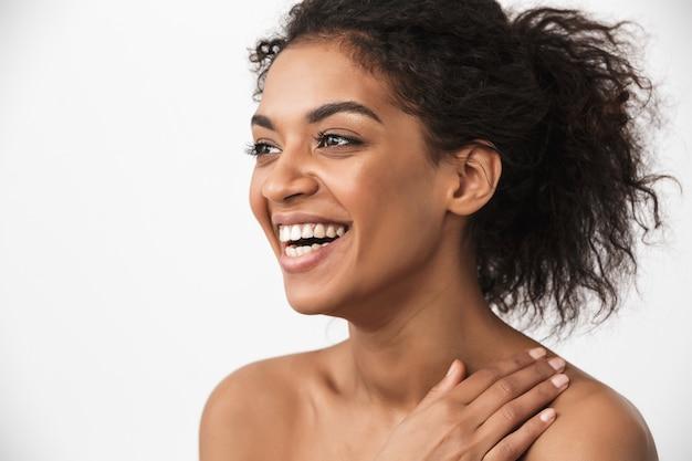 Retrato de uma linda feliz rindo jovem africana posando isolado sobre uma parede branca.