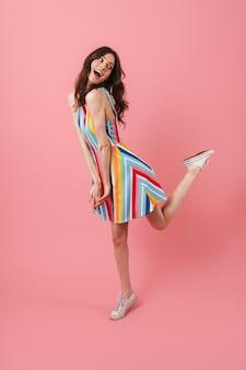 Retrato de uma linda fofa feliz positiva jovem fofa posando isolado na parede rosa pulando
