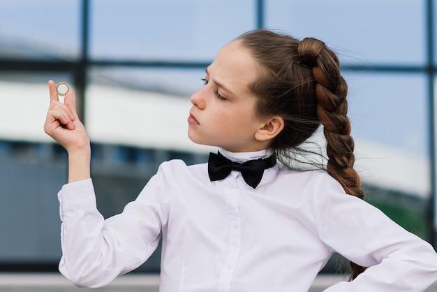 Retrato de uma linda garota adolescente caucasiana segurando moedas. economizando dinheiro e o conceito de negócio.