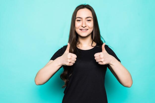 Retrato de uma linda garota adorável, alegre, de cabelos lisos, mostrando o polegar isolado sobre uma parede turquesa