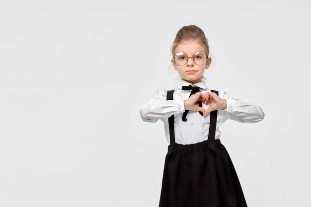 Retrato de uma linda garota adorável encantadora em uniforme escolar, mostrando o gesto do coração
