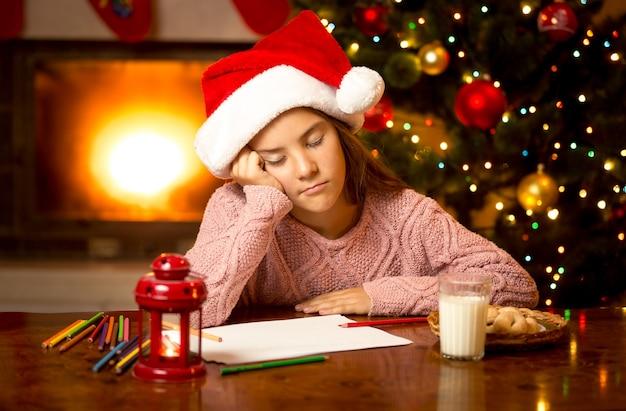 Retrato de uma linda garota adormeceu enquanto escrevia uma carta para o papai noel