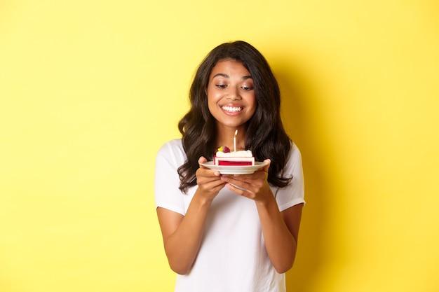 Retrato de uma linda garota afro-americana comemorando aniversário, sorrindo e parecendo feliz com um bolo de aniversário
