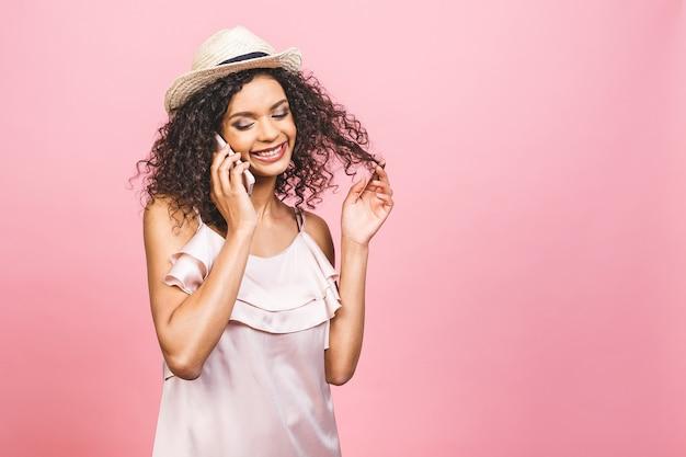 Retrato de uma linda garota afro-americana feliz no vestido, falando no celular e rindo isolado sobre fundo rosa.