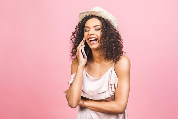 Retrato de uma linda garota afro-americana feliz num vestido falando no celular