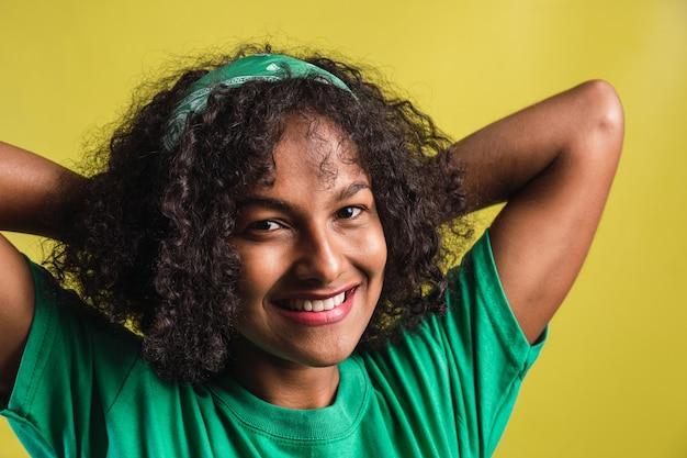 Retrato de uma linda garota afro sorridente com cachos.