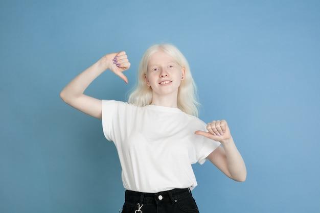 Retrato de uma linda garota albina caucasiana isolada em uma parede azul
