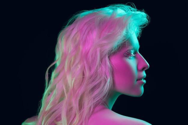 Retrato de uma linda garota albina isolada no fundo escuro do estúdio com luz de néon