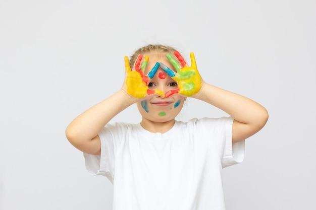 Retrato de uma linda garota alegre com as mãos pintadas, isolado sobre o branco