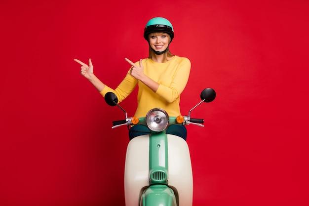 Retrato de uma linda garota alegre e feliz andando de motocicleta, mostrando o espaço