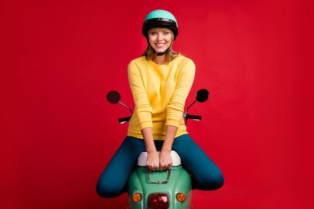 Retrato de uma linda garota alegre sentada na motocicleta com sorriso radiante