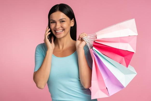 Retrato de uma linda garota animada, vestindo roupas casuais, conversando no smartphone enquanto segura sacolas de compras isoladas sobre fundo rosa