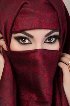 Retrato de uma linda garota árabe escondendo o rosto atrás de um niqab vermelho com um ornamento estampado