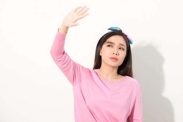 Retrato de uma linda garota asiática, cobrindo o rosto com a mão da luz do sol. mulher com um vestido rosa protegendo o rosto da luz solar
