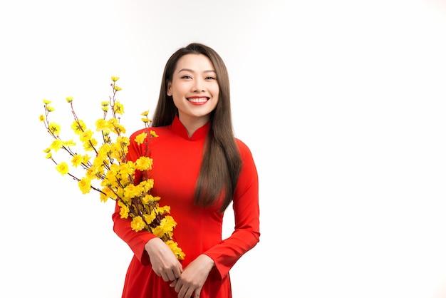 Retrato de uma linda garota asiática em ao dai com flor amarela de damasco no festival tradicional