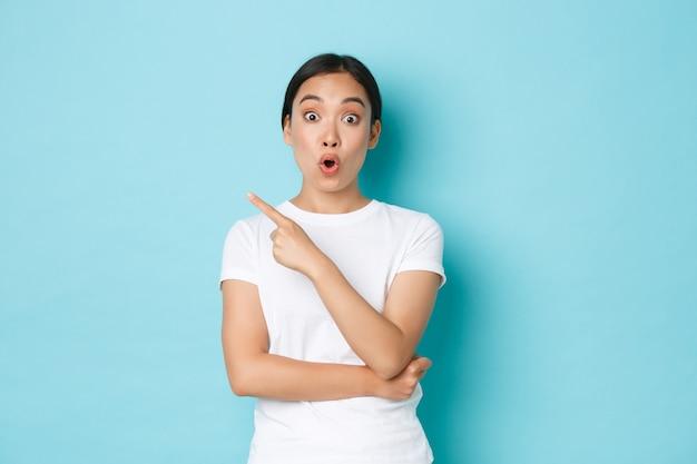 Retrato de uma linda garota asiática espantada dos anos 20 ofegando, fazendo beicinho e dizendo uau enquanto aponta no canto superior esquerdo, mostrando a oferta promocional, fazendo perguntas sobre o anúncio, em pé na parede azul