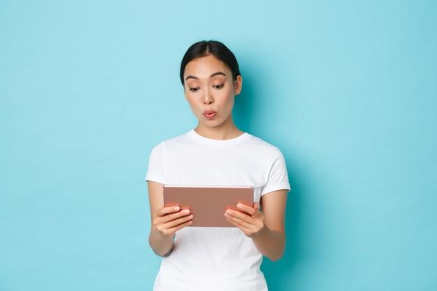 Retrato de uma linda garota asiática impressionada e interessada escolhendo alguém na loja online, olhando pensativo e curioso para a tela do tablet digital, fazendo beicinho como em pé sobre um fundo azul claro.