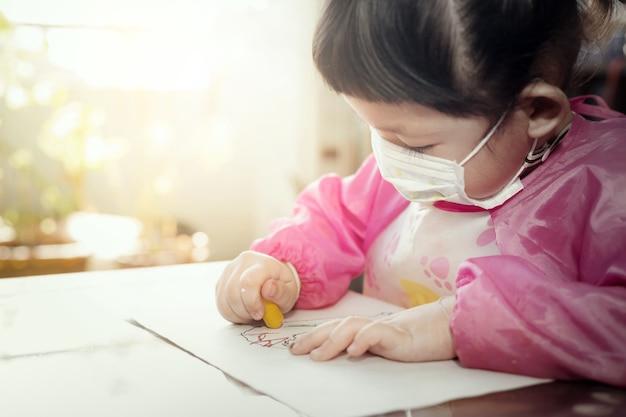 Retrato de uma linda garota asiática usando máscara higiênica facial e desenhando seu trabalho de arte com giz de cera, foco seletivo. quarentena, isolamento domiciliar durante a pandemia de covid-19.