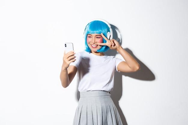 Retrato de uma linda garota asiática vestida de personagem de anime, posando para selfie com fones de ouvido e peruca curta azul