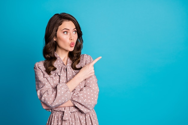 Retrato de uma linda garota atônita com lábios rechonchudos indicando vendas com desconto anúncios promoção ponto dedo indicador copyspace vestir camisa pontilhada isolada sobre fundo de cor azul