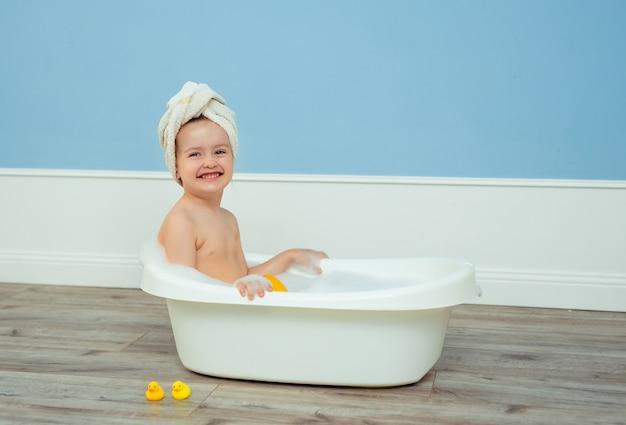 Retrato de uma linda garota bonita com uma toalha com um turbante na cabeça, que toma banho em um banho infantil com espuma e sabão.