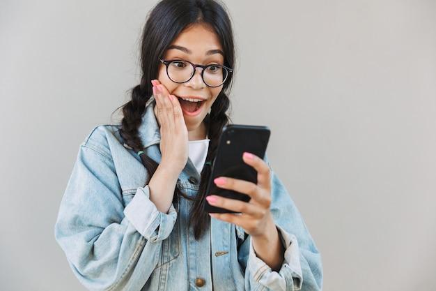 Retrato de uma linda garota bonita fofa chocada na jaqueta jeans, usando óculos isolados sobre uma parede cinza, usando telefone celular.