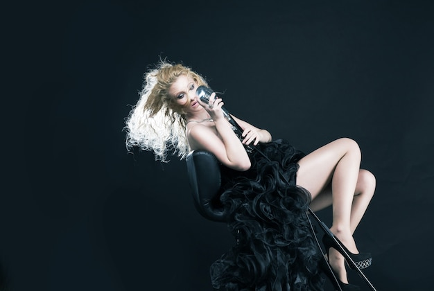 Retrato de uma linda garota cantora em um vestido preto com microfone no palco