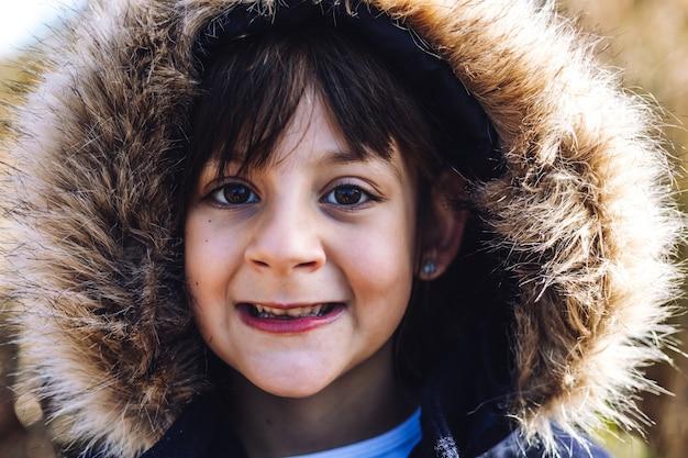 Retrato de uma linda garota caucasiana feliz no parque no inverno