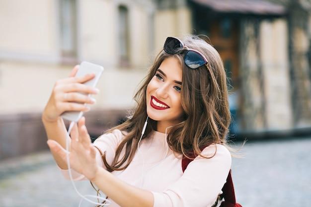 Retrato de uma linda garota com cabelo comprido e lábios vínicos, fazendo selfie na rua da cidade. ela veste uma camisa branca, sorrindo.