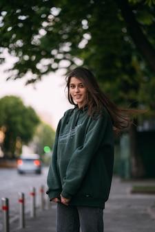 Retrato de uma linda garota com cabelo comprido, posando na rua