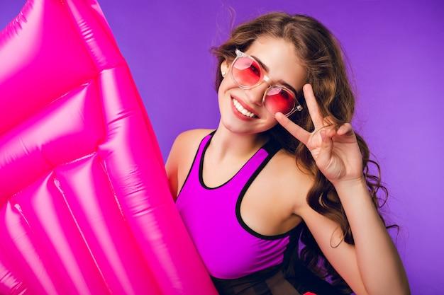 Retrato de uma linda garota com cabelo longo cacheado em óculos de sol rosa, sorrindo para a câmera no fundo roxo no estúdio. ela usa maiô, segura colchão de ar rosa e mostra uma placa de legal.