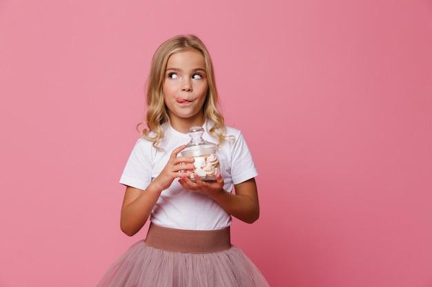 Retrato de uma linda garota com fome segurando o frasco de marshmallow