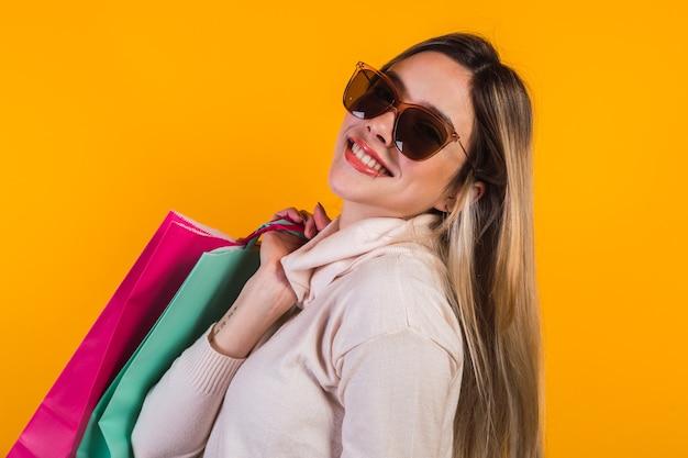 Retrato de uma linda garota com óculos de sol, feliz com sacolas de compras.