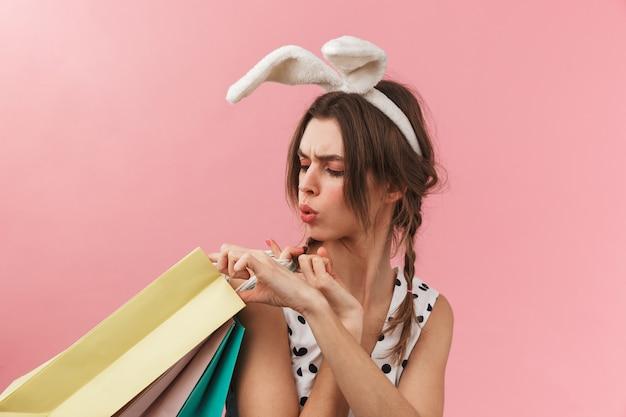 Retrato de uma linda garota com orelhas de coelho, isolada, carregando sacolas de compras