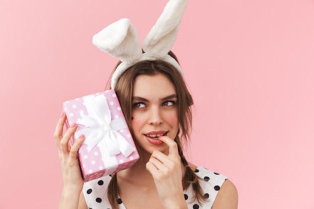 Retrato de uma linda garota com orelhas de coelho, isolada, segurando uma caixa de presente