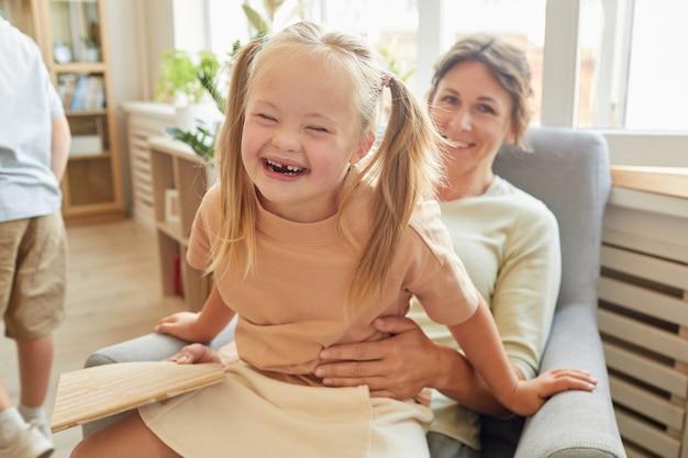 Retrato de uma linda garota com síndrome de down rindo alegremente enquanto brincava com a mãe em casa