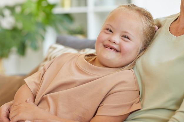 Retrato de uma linda garota com síndrome de down, sorrindo alegremente para a câmera com uma mãe irreconhecível abraçando-a, copie o espaço