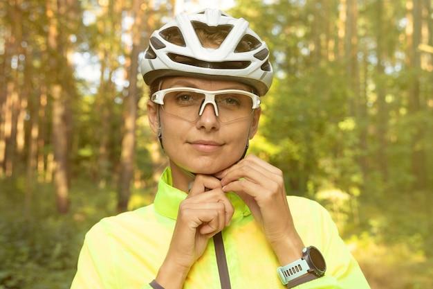 Retrato de uma linda garota com um blusão verde brilhante e óculos que corrigem o capacete